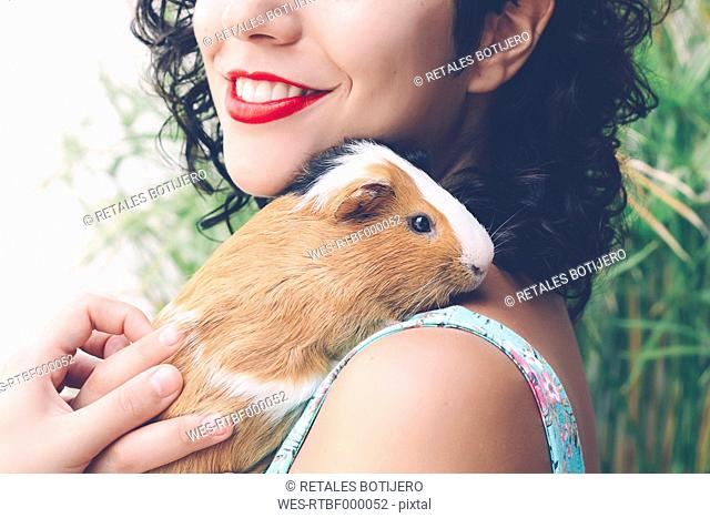 Young woman with Guinea pig on her shoulder