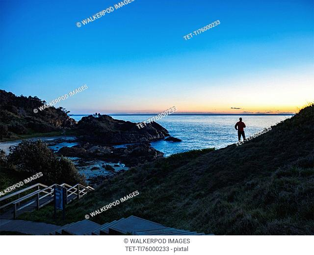 Australia, New South Wales, Port Macquarie, Silhouette of man looking at sea at sunrise