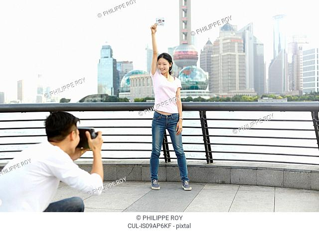 Female tourist holding instant photo posing for boyfriend with instant camera, The Bund, Shanghai, China