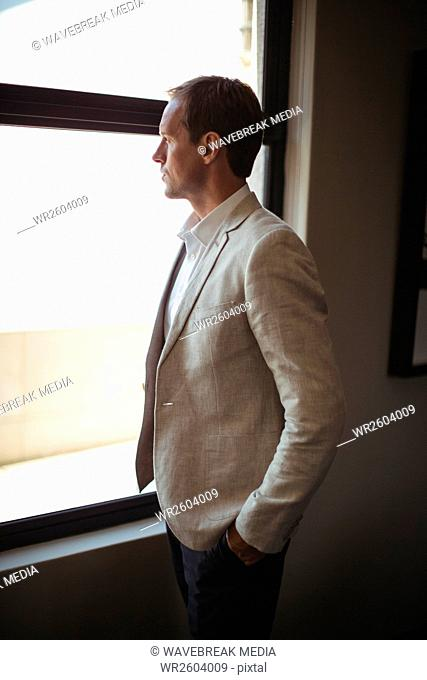Thoughtful businessman looking through window