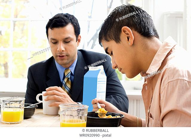Man and boy at breakfast table displeased