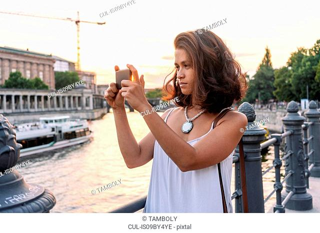 Female student taking photograph with smartphone by river, Berlin, Germany