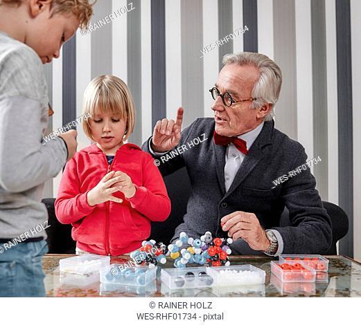Grandfather and grandchildren with molecular model