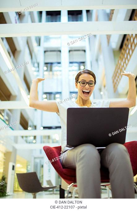 Businesswoman getting excited in office building