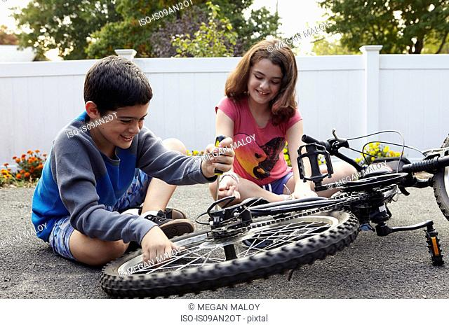 Brother and sister repairing bicycle on driveway
