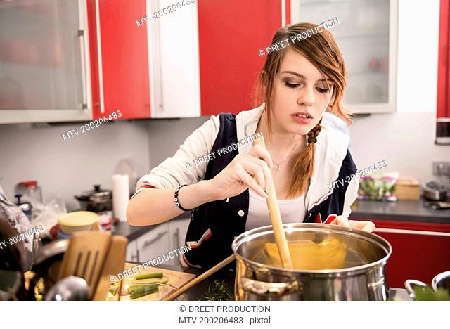 Young woman cooking in the kitchen, Munich, Bavaria, Germany
