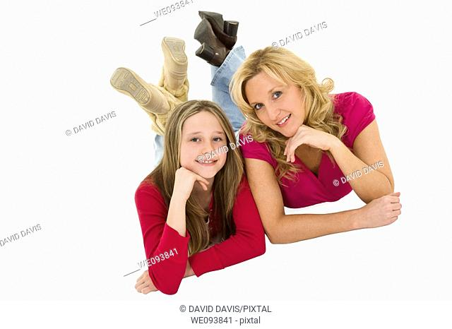 Mother and daughter laying on a white background together in casual clothing