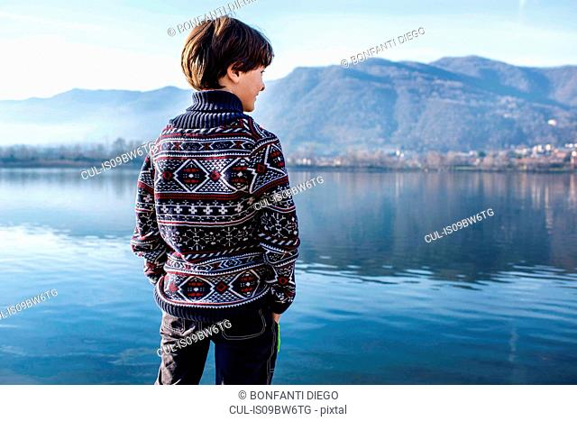 Boy looking out from lakeside, rear view, Lake Como, Lecco, Lombardy, Italy