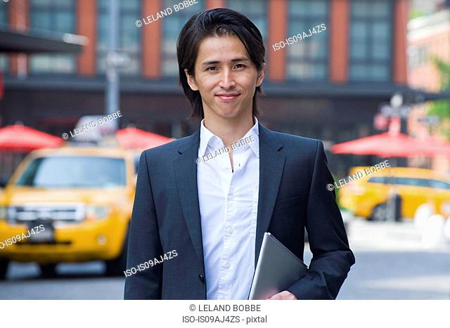 Mid adult businessman walking on city street carrying digital pad