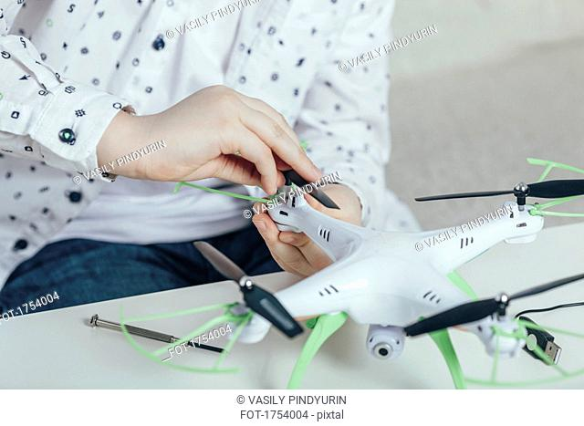 Midsection of boy adjusting drone at home