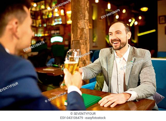 Cheerful business partners wearing suits sitting at cafe table and clinking beer glasses together after successful completion of negotiations