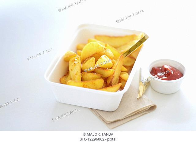 Chips and ketchup in takeaway cartons