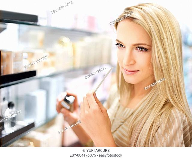 An attractive young woman thinking about whether to purchase a particular perfume