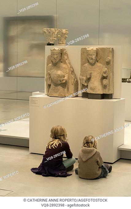 Two light haired children sat cross legged in front of two light stone crowned figure carvings, listening to historical commentaries, Louvre-Lens Museum