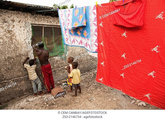 Man repairing the window of his house and children following him carefully, Jambiani, Zanzibar Island, Tanzania, East Africa