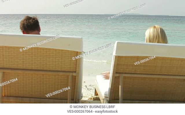 Couple lying on sun loungers before getting up and sitting in sea.Shot on Canon 5d Mk2 with a frame rate of 30fps