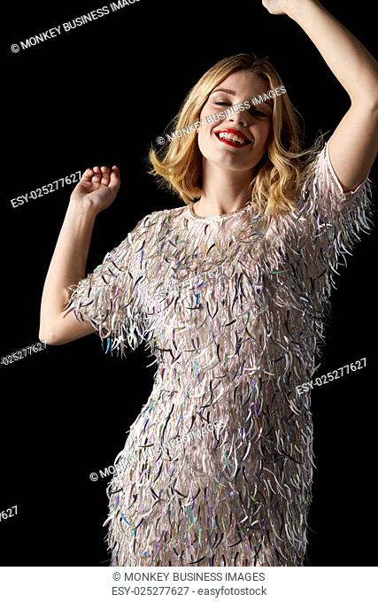Glamorous blonde woman dancing, arms raised and eyes closed