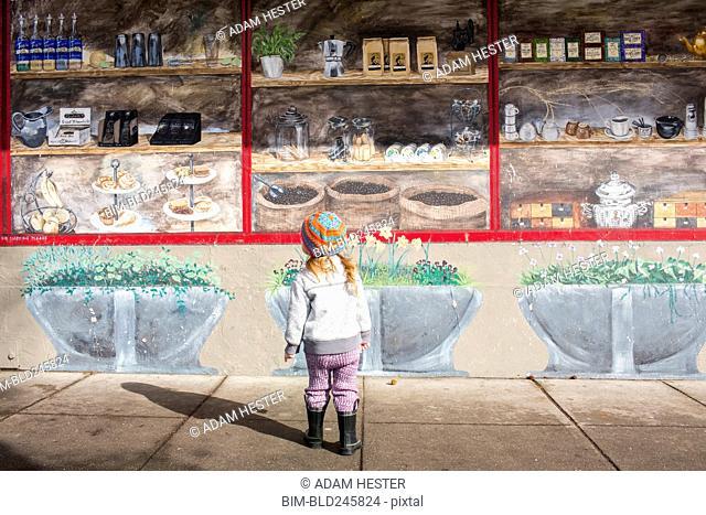 Caucasian girl standing on sidewalk admiring mural on wall