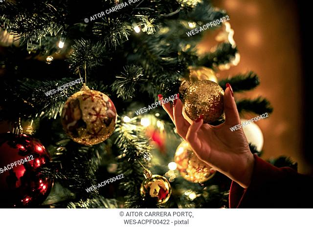 Female hand holding golden Christmas bauble, close-up