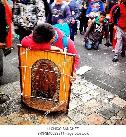 A pilgrims rests as he kneels carrying an image of the Virgin of Guadalupe during the anual pilgrimage to Our Lady of Guadalupe Basilica in Mexico City, Mexico