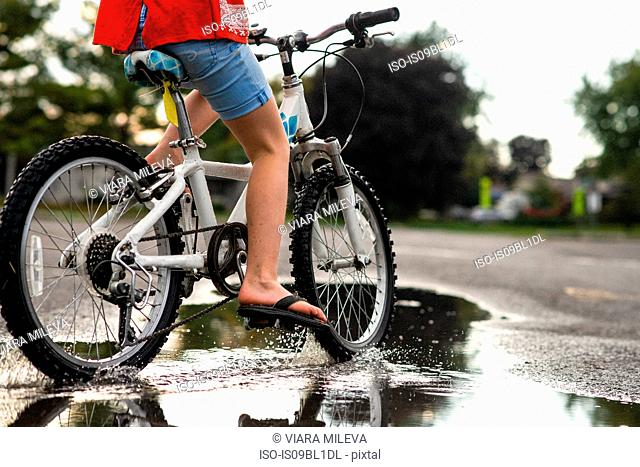 Girl riding bicycle on wet road