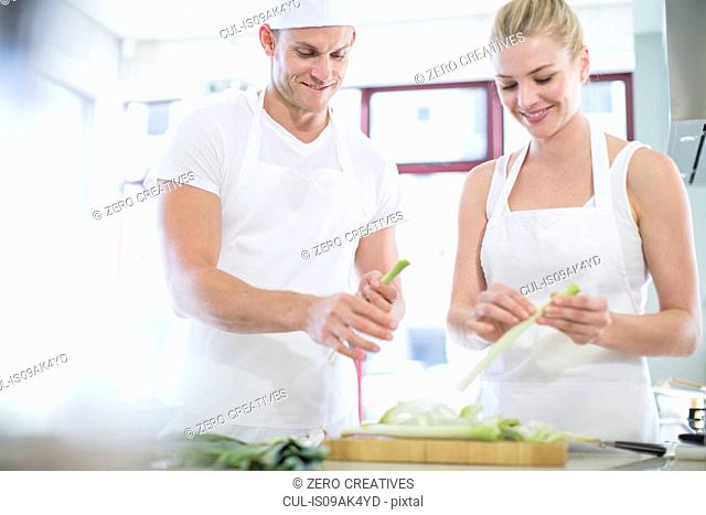 Male and female chefs peeling leeks in commercial kitchen
