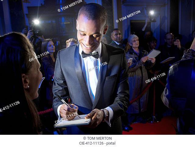 Well dressed celebrity signing autograph on red carpet