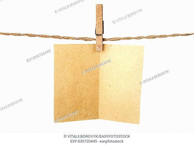 Piece old sheet of paper on clothespins isolated on white background