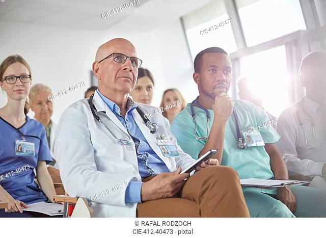 Attentive surgeons, doctors and nurses listening in conference