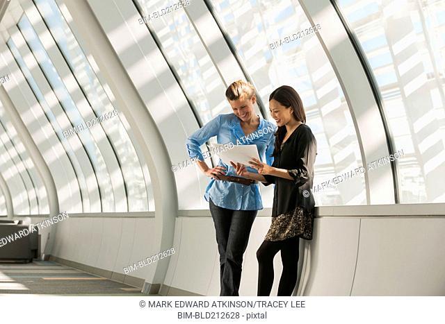 Businesswomen reading paperwork in lobby