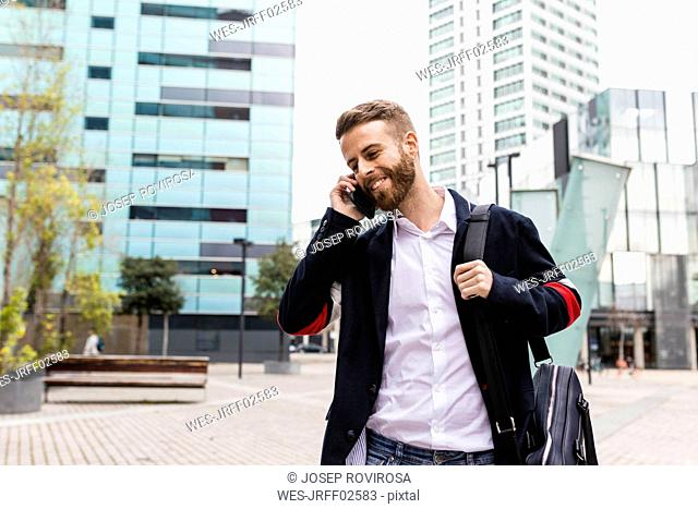 Stylish businessman talking on cell phone in the city
