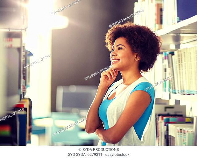 african student girl looking for book at library