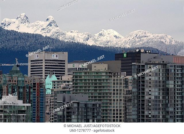 Vancouver's skyline is dwarfed by the local snow-covered mountains in British Columbia, Canada