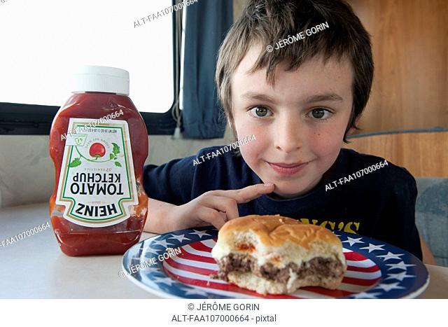Boy with hamburger, portrait