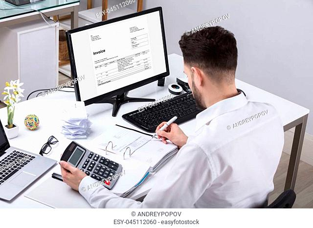 Young Businessman Calculating Tax With Calculator At Desk