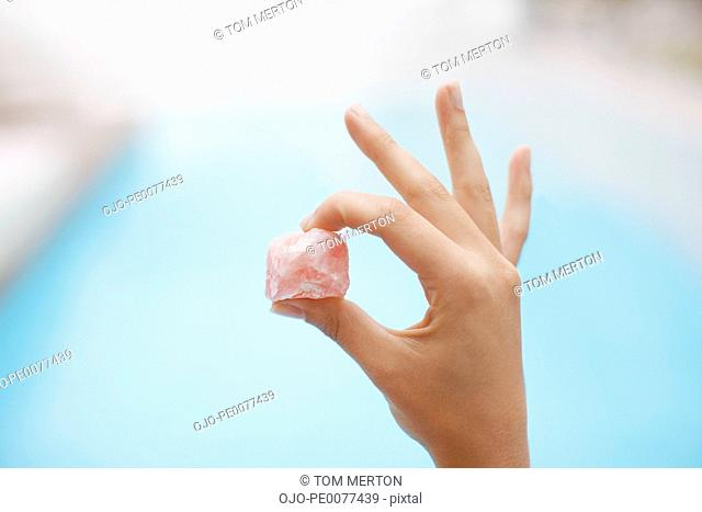 Hand holding crystal at poolside