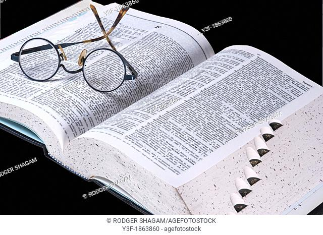 A pair of spectacles lies on the pages of an open dictionary
