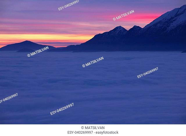 Sea of fog over an alpine lake with snow-capped mountain in sunset