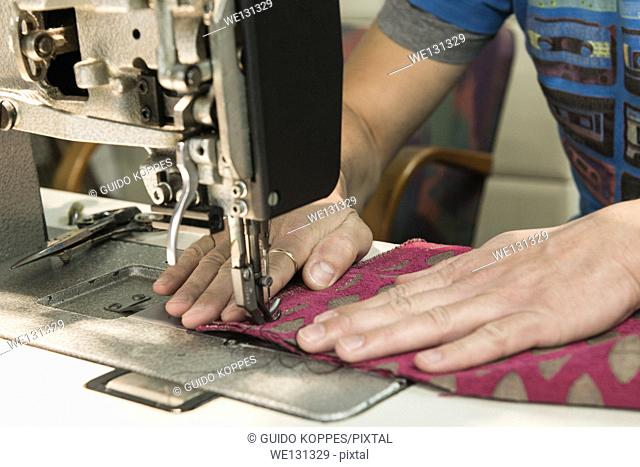 Tilburg, Netherlands. Hands of the 37 year old upholsterer 'Josef', handling a piece of cloth and a sewing machine