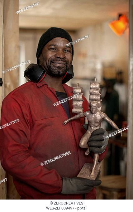 Smiling man holding bronze figurine