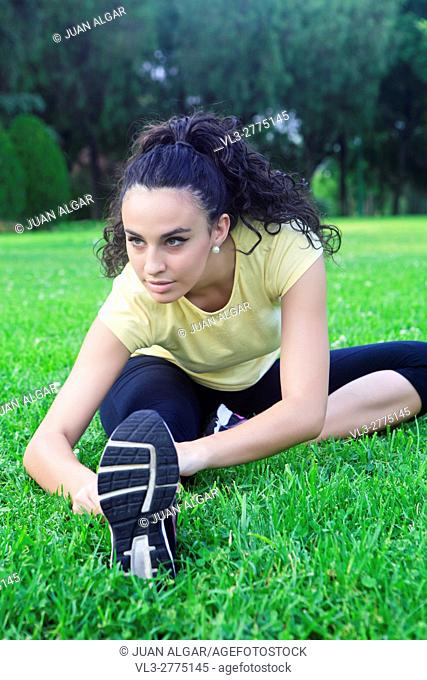 Portrait of beautiful sportswoman stretching on grass in park. Bokeh
