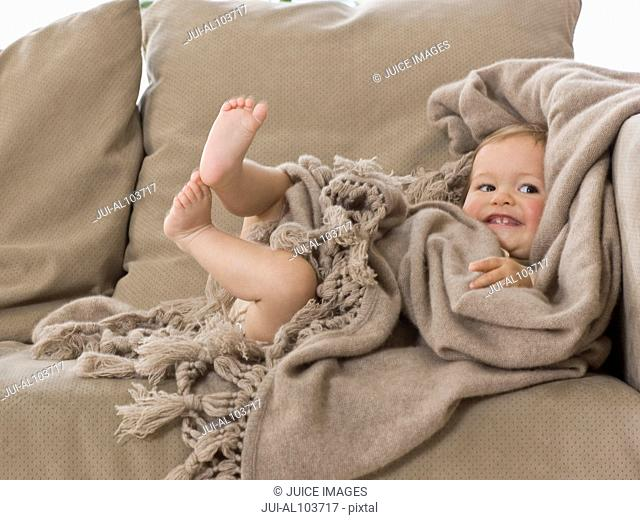 A young child sitting on a sofa wrapped up in a blanket smiling