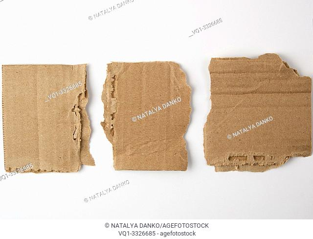 three pieces of torn brown paper on a white background, close up