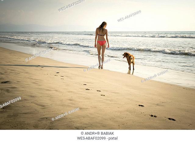 Mexico, Riviera Nayarit, Woman walking with dog at the beach