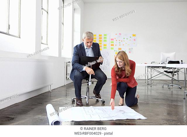 Businessman and woman in office looking at construction plan