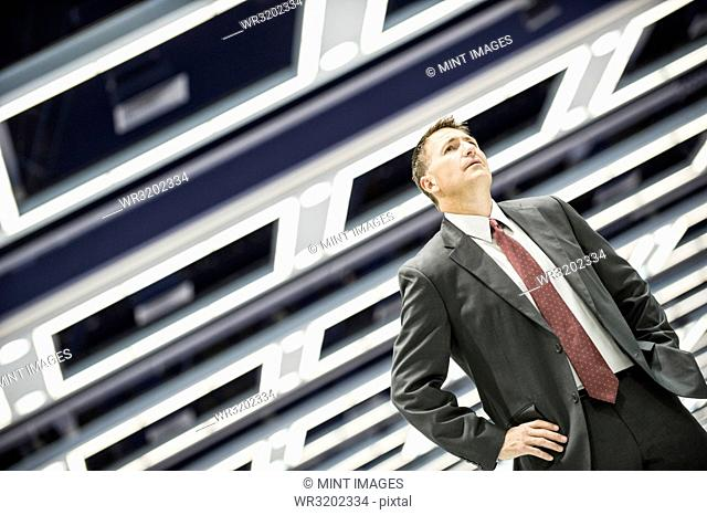 A view looking up at a Caucasian businessman walking through a convention centre arena