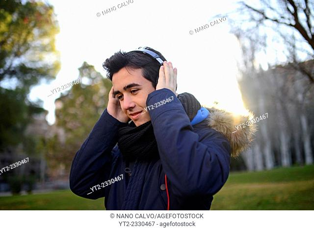 Exterior portrait of teenager listening to music with headphones and portable device