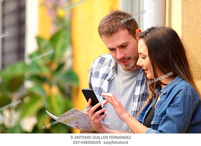 Two serious tourists checking smart phone and map on vacation