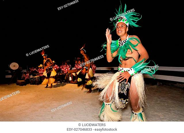 Polynesian Pacific Island Tahitian male dancers in colorful costume dancing on tropical beach.Photo by Rafael Ben-Ari/Chameleons Eye