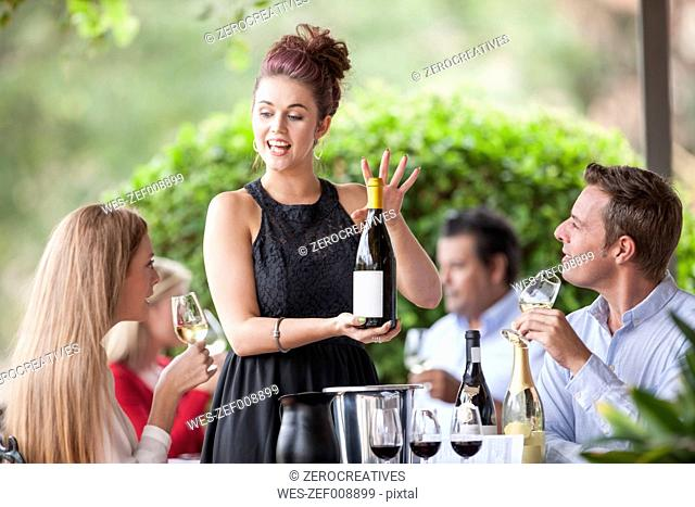 Waitress showing wine bottle to clients in restaurant
